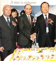 Image: Qatar Airways executives cut a cake at a welcoming ceremony at Baiyun International Airport