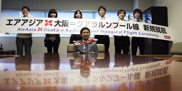 Posing with the sign from the Osaka to Kuala Lumpur launch event were Akiko Tonoshita, Midori Kitagawa, Kanako Kinoshita, Takahiro Deo, Masato Kubota and Takashi Yoshimura, while Takahiro Ozeki, Acting General Manager, is seated by the airline's aircraft model.