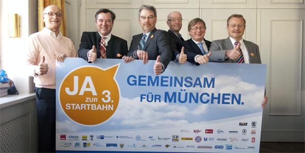 Bernhard Loos (Citizen's Initiative for Runway 3), Josef Schmid (CSU), Alexander Reissl (SPD) Michael Mattar (FDP), Michael Kerkloh (Munich Airport) and Manfred Rothkopf (IHK) pictured standing behind a banner advertising Munich Airports' planned runway 3.